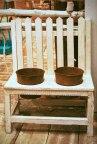 Banco de madera blanca con maceteros.