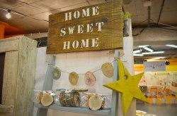 """Cartel XL con mensaje """"Home Sweet Home"""", guirnalda de rebanadas de madera y estrella de madera para colgar."""