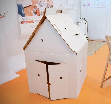 Casa cabaña de cartón para jugar, pintar y decorar. Tiene puerta y siete ventanas, para que los niños se lo pasen pipa asomándose desde dentro.